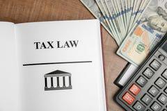 Calculadora, dinheiro e livro com palavras LEI FISCAL foto de stock royalty free