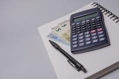 Calculadora, dinheiro, pena e caderno na tabela do escritório no fundo branco Conceito do orçamento Foto de Stock Royalty Free