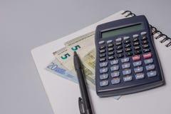 Calculadora, dinheiro, pena e caderno na tabela do escritório no fundo branco Conceito do orçamento Fotos de Stock