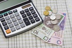 Calculadora, dinheiro polonês e jornal Foto de Stock