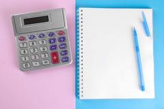 Calculadora e caderno com pena em um fundo azul e cor-de-rosa stationery imagens de stock
