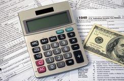 Calculadora e dinheiro em formulários de imposto da renda Imagens de Stock