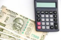 Calculadora e indio a estrenar 500 rupias de billetes de banco en el fondo blanco