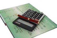 Calculadora e livro Imagem de Stock