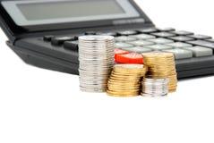 Calculadora e moedas de encontro ao fundo branco Imagens de Stock Royalty Free