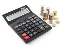 Calculadora e moedas isoladas no fundo branco fotografia de stock royalty free