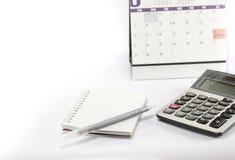 A calculadora e a pena e o caderno são calendário próximo Imagem de Stock