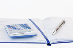 Calculadora e pena em um diário Fotografia de Stock Royalty Free