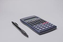 Calculadora e pena na tabela do escritório no fundo branco Conceito do orçamento Fotos de Stock