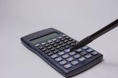 Calculadora e pena na tabela do escritório no fundo branco Conceito do orçamento Fotografia de Stock Royalty Free