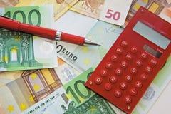 Calculadora e pena vermelhas no fundo das notas de banco Fotografia de Stock Royalty Free