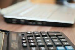 Calculadora e portátil na tabela Foto de Stock
