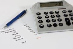 Calculadora e uma pena junto com um orçamento negativo Imagem de Stock