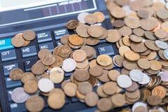 Calculadora e uma pilha de moedas Imagem de Stock