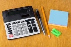Calculadora eletrônica, papel, pena, apontador e lápis Fotografia de Stock Royalty Free