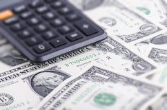 Calculadora em notas de dólar Imagens de Stock