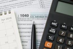 Calculadora en calendario, pluma y formulario del impuesto sobre la renta de los 1040 E.E.U.U., presentación del impuesto o conce imagen de archivo libre de regalías