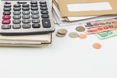 Calculadora en el cuaderno, pila de correo, monedas y billetes de banco en el fondo blanco Imagen de archivo libre de regalías