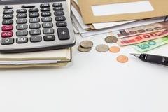 Calculadora en el cuaderno, pila de correo, monedas y billetes de banco en el fondo blanco Imágenes de archivo libres de regalías