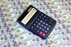 Calculadora en el fondo de cientos billetes de dólar Fotografía de archivo