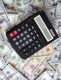 Calculadora en el fondo de cientos billetes de dólar Imagenes de archivo