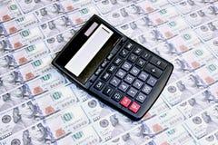 Calculadora en el fondo de cientos billetes de dólar Imágenes de archivo libres de regalías