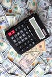 Calculadora en el fondo de cientos dólares de cuentas Fotografía de archivo