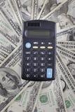 Calculadora en el fondo de los billetes de banco americanos de los dólares Fotografía de archivo libre de regalías