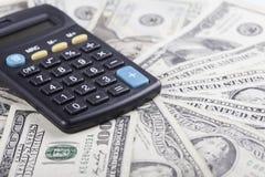 Calculadora en el fondo de los billetes de banco americanos de los dólares Foto de archivo