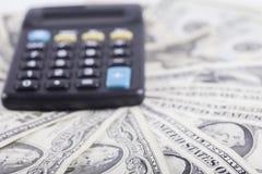Calculadora en el fondo de los billetes de banco americanos de los dólares Imagen de archivo