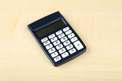 Calculadora en el fondo de madera, cierre para arriba Imagen de archivo libre de regalías