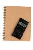 Calculadora en el libro con la portada del alambre espiral Imagenes de archivo