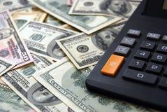 Calculadora en fondo del dinero Imagenes de archivo