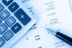 Calculadora en informe financiero con el fondo azul Imagen de archivo libre de regalías