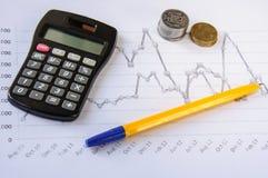 Calculadora en la pluma del escritorio, cálculos, carta, monedas Imágenes de archivo libres de regalías