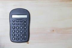 Calculadora en la tabla de madera Imagen de archivo