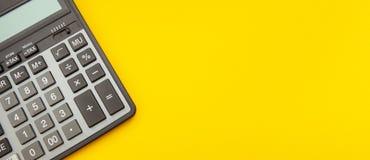 Calculadora en un fondo amarillo estirado con el espacio para el concepto del texto, del negocio y de las finanzas foto de archivo libre de regalías