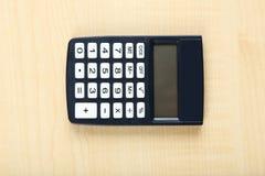 Calculadora en un fondo de madera Foto de archivo