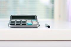 Calculadora en una tabla blanca Imagen de archivo
