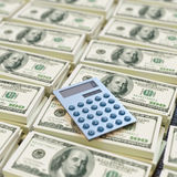 Calculadora encima de billetes de dólar Imagen de archivo