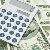 Calculadora encima de billetes de dólar Foto de archivo libre de regalías