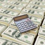 Calculadora encima de billetes de dólar Imagenes de archivo