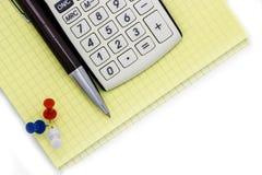 A calculadora encontra-se em um bloco de notas, ao lado da pena fotos de stock