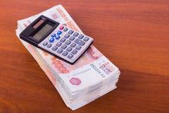 A calculadora encontra-se em um punhado grande do dinheiro Fotografia de Stock Royalty Free