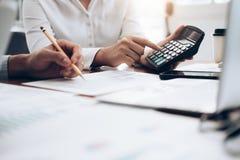 Calculadora fêmea do uso do contador ou do banqueiro imagem de stock