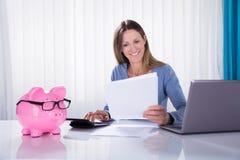 Calculadora feliz de Calculating Invoice Using de la empresaria fotografía de archivo libre de regalías