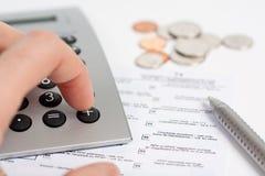 Calculadora, forma de impuesto, pluma y monedas Imagen de archivo