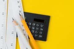 Calculadora, lápices y cintas métricas blancas con centímetro y pulgadas en fondo, longitud, largo amarillos vivos o fabricante fotografía de archivo