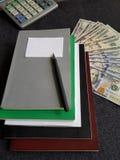 calculadora, libros y 100 billetes de dólar Foto de archivo