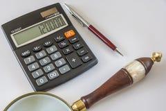 Calculadora, lupa, y bolígrafo Pen On White Background Foto de archivo